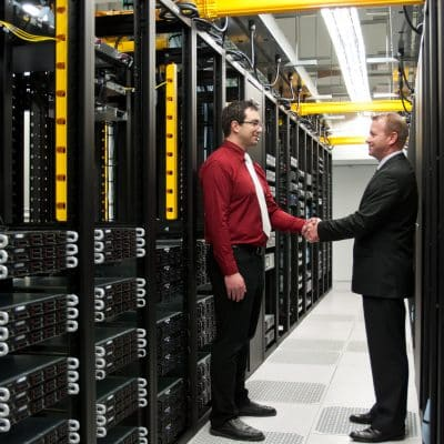 two men shaking hands in a server room